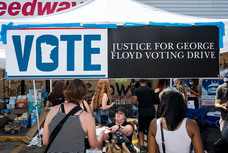 """People fill out voter registration forms at a memorial site for George Floyd on June 3, 2020 in Minneapolis, Minnesota. <p class=""""copyright"""">Stephen Maturen/Stringer/Getty Images</p>"""
