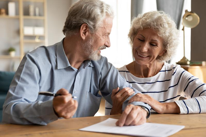 70s couple sit at table indoor discuss agreement term and condition feels satisfied make financial deal ready to sign contract, bequeath savings and property to their children or grandchildren concept