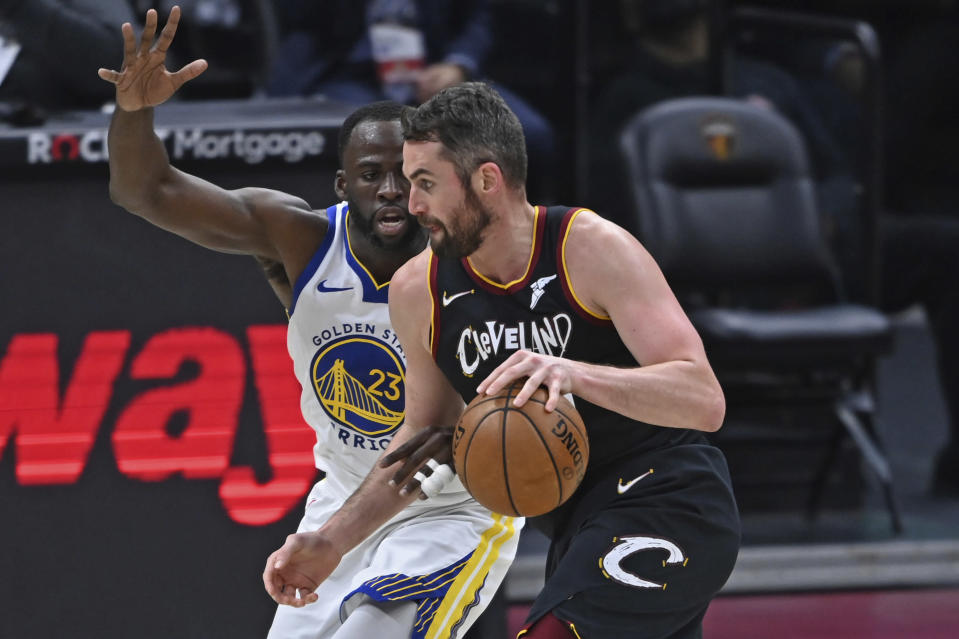 Cleveland Cavaliers' Kevin Love, right, drives against Golden State Warriors' Draymond Green (23) in the second half of an NBA basketball game, Thursday, April 15, 2021, in Cleveland. (AP Photo/David Dermer)