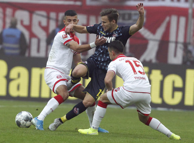 Duesseldorf's Alfredo Morales, left, and Erik Thommy, right, challenge for the ball with Cologne's Louis Schaub, center, during the German Bundesliga soccer match between Fortuna Duesseldorf and 1.FC Cologne in Duessledorf, Germany, Sunday, Nov. 3, 2019. (Roland Weihrauch/dpa via AP)