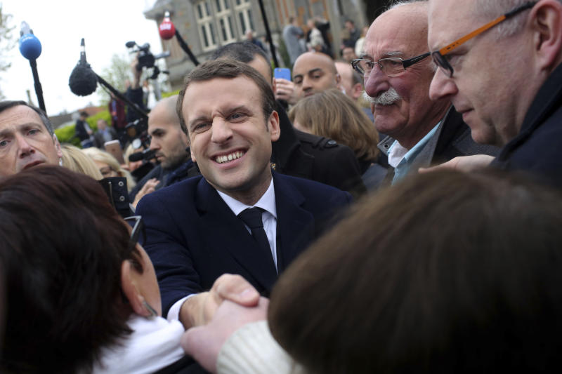 Centrist candidate Emmanuel Macron shakes hands with a supporter after casting his ballot in the first round of the French presidential election, in le Touquet, northern France, Sunday, April 23, 2017. (AP Photo/Thibault Camus)