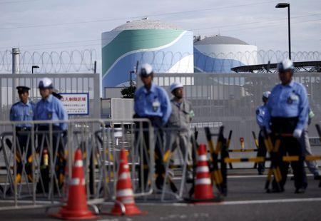 Security personnel stands guard in front of an entrance gate of Kyushu Electric Power's Sendai nuclear power station in Satsumasendai, Kagoshima prefecture, Japan, August 7, 2015. REUTERS/Issei Kato