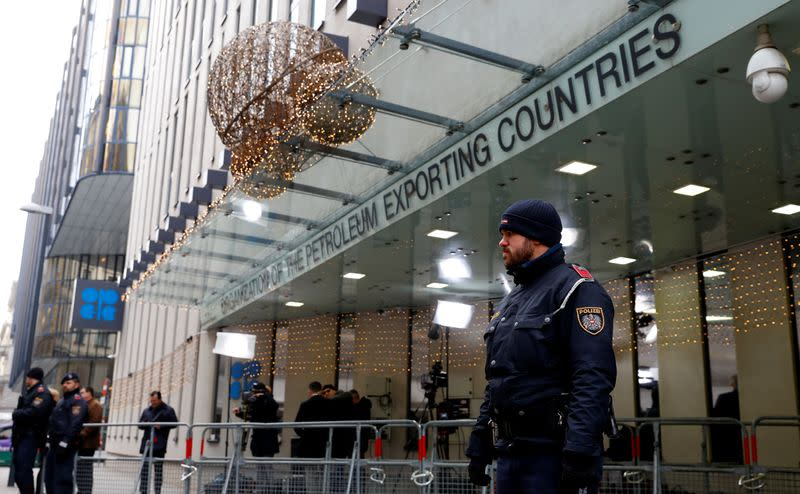 Journalists and police officers stand outside the Organisation of the Petroleum Exporting Countries (OPEC) headquarters in Vienna