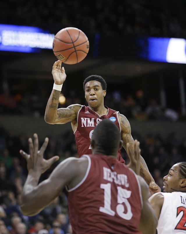 New Mexico State's Daniel Mullings leaps to pass to Tshilidzi Nephawe in the first half against San Diego State during a second-round game of the NCAA men's college basketball tournament in Spokane, Wash., Thursday, March 20, 2014. (AP Photo/Elaine Thompson)