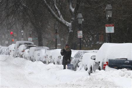 A driver works to dig a car out of the snow during a winter nor'easter snow storm in Boston, Massachusetts January 3, 2014. REUTERS/Brian Snyder