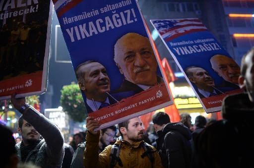 A Turkish protester holds up a placard with pictures of Recep Tayyip Erdogan (left) and Fethullah Gulen during a demonstration against corruption in the Kadikoy district of Istanbul on December 25, 2013