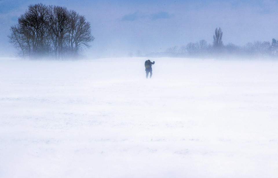 A man walks across a snow-covered field on the island of Ruegen, Germany, Sunday, Feb. 7, 2021. Strong winds are causing snow drifts in the north of the island. The German Weather Service (DWD) expects snowstorms and permafrost for northern Germany this weekend. (Jens Buettner/dpa via AP)