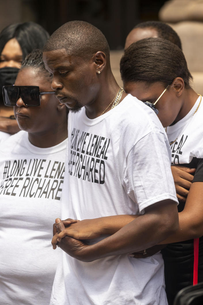 From left, Lanesha Frazier, 22, daughter of Leneal Frazier; Orlando Frazier, brother of Leneal; and Jamie Bradford, 20, daughter of Leneal, comfort each other during a news conference outside of City Hall, Friday, July 9, 2021, in Minneapolis. Leneal Frazier was killed earlier in the week after his vehicle was struck by a squad car that police said was pursuing another driver linked to several robberies. Frazier was not involved in the pursuit. (Antranik Tavitian/Star Tribune via AP)