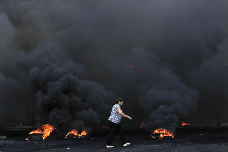 A woman walks by burning tires that were set fire to block a road during a protest against government's plans to impose new taxes in Beirut, Lebanon, Friday, Oct. 18, 2019. The protests erupted over the government's plan to impose new taxes during a severe economic crisis, with people taking their anger out on politicians they accuse of corruption and decades of mismanagement. (AP Photo/Hassan Ammar)