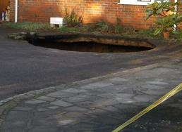 Handout photo issued by Buckinghamshire Fire and Rescue Service of a A 30ft deep sinkhole which has opened up in the driveway of a house. PRESS ASSOCIATION Photo. Issue date: Sunday February 2, 2014. Firefighters were called to the property in Main Road, Walter's Ash, High Wycombe, Buckinghamshire, at 8.32am where they found the hole which is 15ft in diameter. See PA story ENVIRONMENT Sinkhole. Photo credit should read: Buckinghamshire Fire and Rescue Service/PA Wire  NOTE TO EDITORS: This handout photo may only be used in for editorial reporting purposes for the contemporaneous illustration of events, things or the people in the image or facts mentioned in the caption. Reuse of the picture may require further permission from the copyright holder.