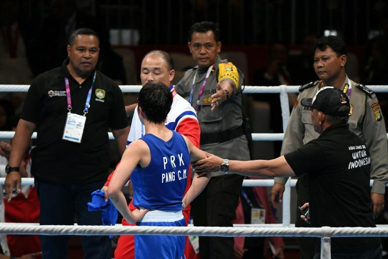 Police and security step into the ring to end a protest by North Korea coach Pak Chol Jun and boxer Pang Chol Mi