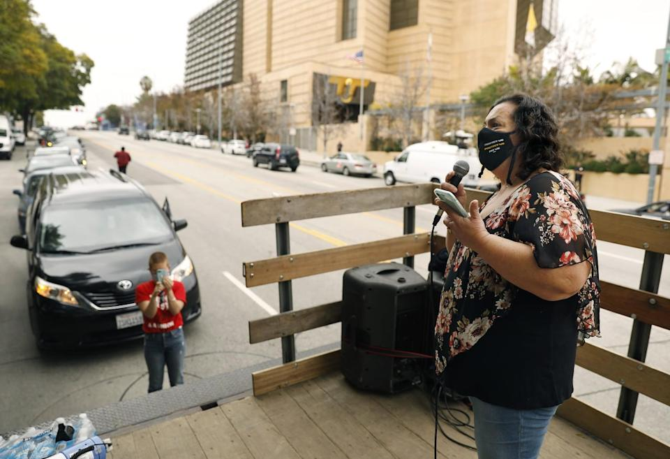 Imelda Rosales, a McDonald's janitor, talks into a microphone at a protest over COVID-19 safety.