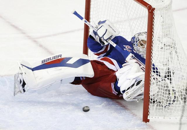The puck, shot by Los Angeles Kings right wing Dustin Brown, bounces back out of the net after a goal as New York Rangers goalie Henrik Lundqvist (30) falls backward in the second period during Game 4 of the NHL hockey Stanley Cup Final, Wednesday, June 11, 2014, in New York. (AP Photo/Frank Franklin II)