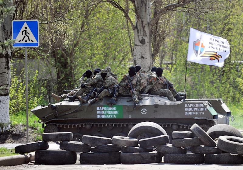 "Men ride on an armoured personnel carrier (APC) with a white flag reading ""People's volunteer corps of Donetsk"" outside the regional state building seized by pro-Russian separatists in the eastern Ukrainian city of Slavyansk on April 18, 2014 (AFP Photo/Genya Savilov)"