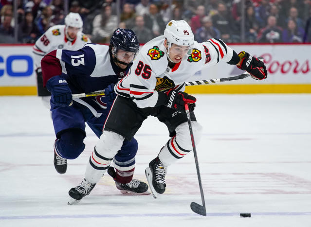 Chicago Blackhawks right wing Dylan Sikura (95) moves the puck against Colorado Avalanche center Alexander Kerfoot (13) during the first period of an NHL hockey game, Saturday, March 23, 2019 in Denver. (AP Photo/Jack Dempsey)