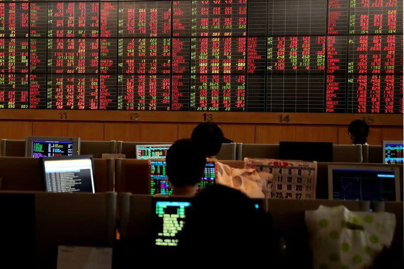 FILE PHOTO: Traders are seen in front of a screen with trading figures in red at Thailand Stock Exchange building in Bangkok