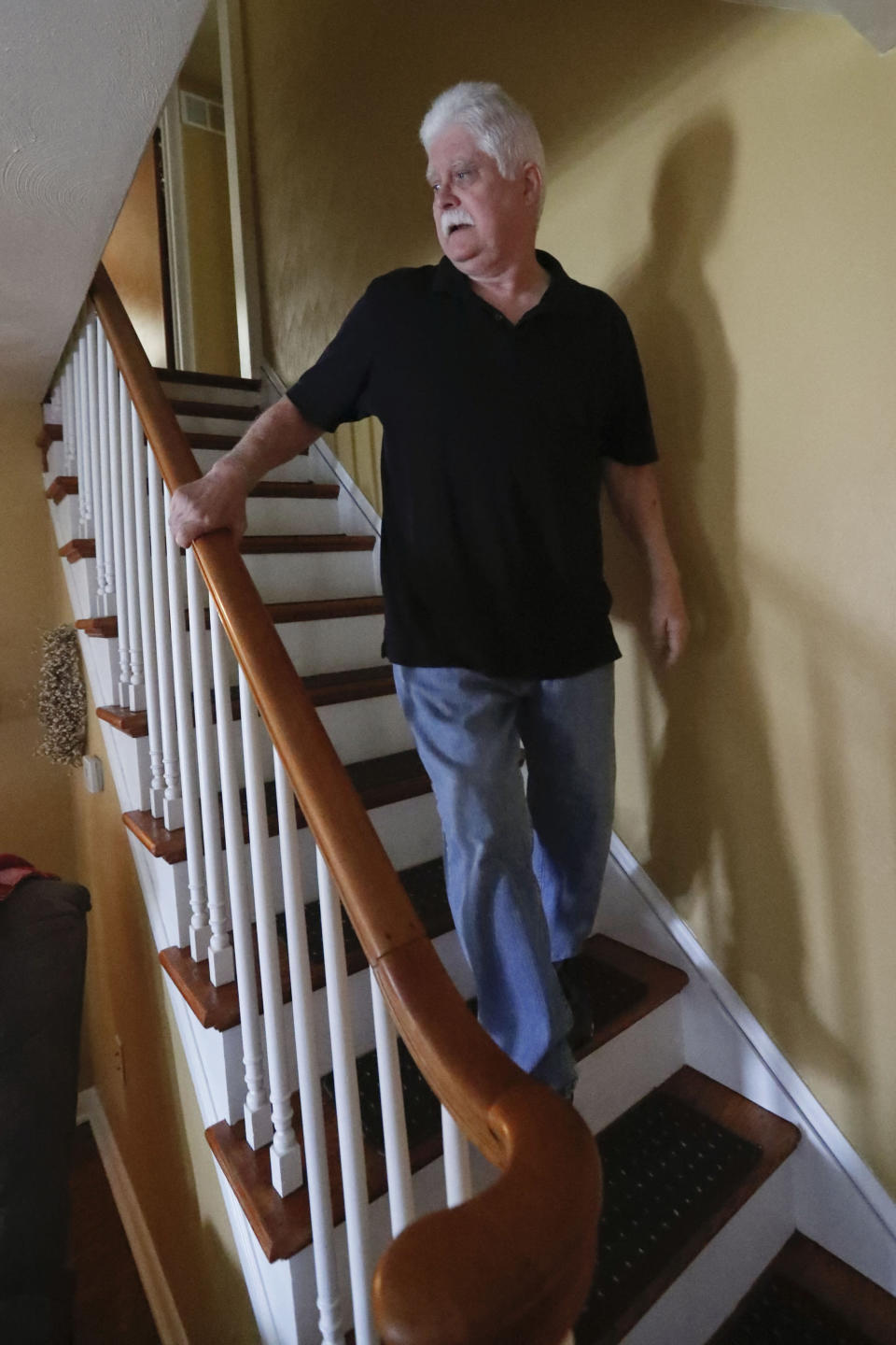 In this April 8, 2019, photo Chuck Pope, who suffers from rheumatoid arthritis, walks down the stairs in his home in Derry, Pa. While he was still working, his insurance covered an injected drug that relieves pain and stops irreversible joint damage but retails for over $5,000 a month. Now his Medicare plan doesn't cover the drug, and Pope says his condition is deteriorating without it. Meanwhile, sales of approved, cheaper versions have been blocked. (AP Photo/Keith Srakocic)