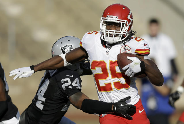 Kansas City Chiefs running back Jamaal Charles (25) runs against Oakland Raiders cornerback Charles Woodson during the second quarter of an NFL football game in Oakland, Calif., Sunday, Dec. 15, 2013. (AP Photo/Ben Margot)