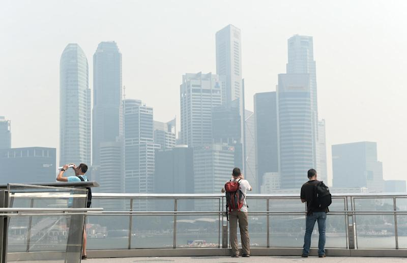 People take pictures from a bridge of the skyline of the financial district in Singapore on June 14, 2013