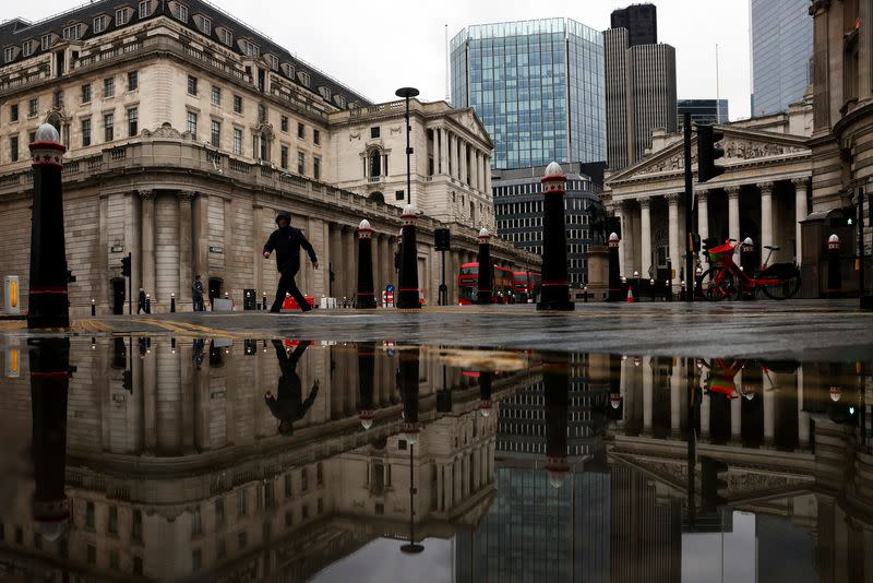 The Bank of England and Royal Exchange are reflected in a puddle as a pedestrian walks past in London