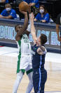 Boston Celtics guard Jaylen Brown (7) shoots as Dallas Mavericks guard Luka Doncic (77) defends during the first half of an NBA basketball game in Dallas, Tuesday, Feb. 23, 2021. (AP Photo/Sam Hodde)