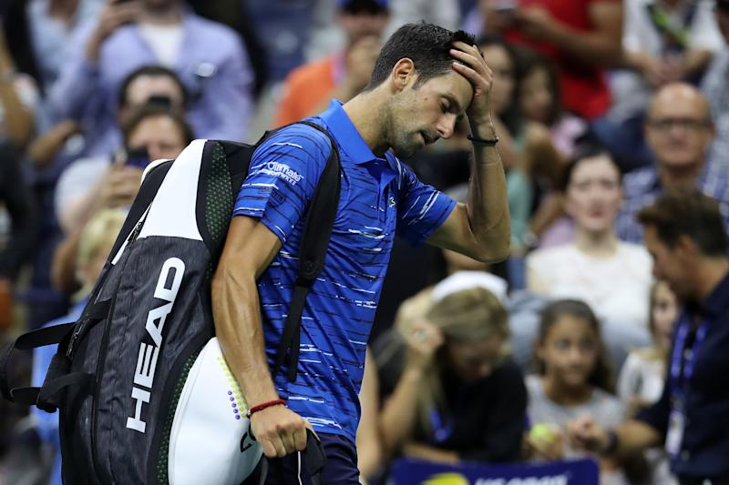 Novak Djokovic reacts as he walks off court after retiring due to a should injury during his fourth round match against Stan Wawrinka at the US Open on Sunday night.