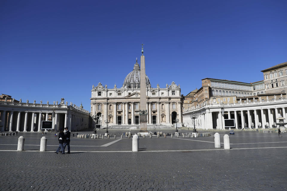Policemen patrol an empty St. Peter's Square at the Vatican, Sunday, April 4, 2021. Italy has entered a three-day strict nationwide lockdown to prevent new surges of the coronavirus. Police set up road checks to ensure people were staying close to home and extra patrols were ordered up to break up large gatherings in squares and parks, which over Easter weekend are usually packed with picnic-goers. (AP Photo/Gregorio Borgia)