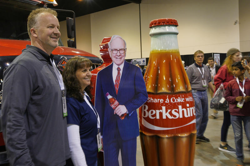 Berkshire Hathaway shareholders pose with a cutout of Chairman and CEO Warren Buffett, at the Coca Cola booth, Friday, May 3, 2019, during a shareholder shopping day, one day before Berkshire Hathaway's annual shareholders meeting. An estimated 40,000 people are expected in town for the event, where Buffett and Munger preside over the meeting and spend hours answering questions. (AP Photo/Nati Harnik)