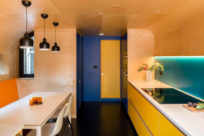 Vibrant yellow cabinetry is bespoke by the contractor; a backsplash clad in turquoise Formica laminate provides a strong contrast. The birch plywood on the walls and ceiling recall the owners' love of modernist designer Alvar Aalto's bent plywood furniture.