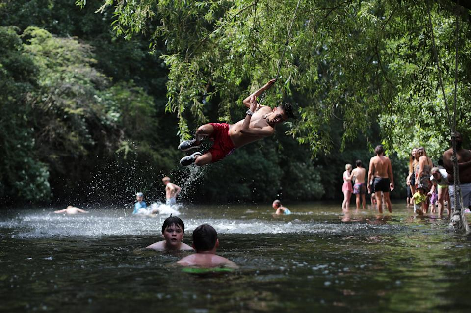 <p>People jumping into the River Lea during last summer's heatwave</p> (REUTERS)