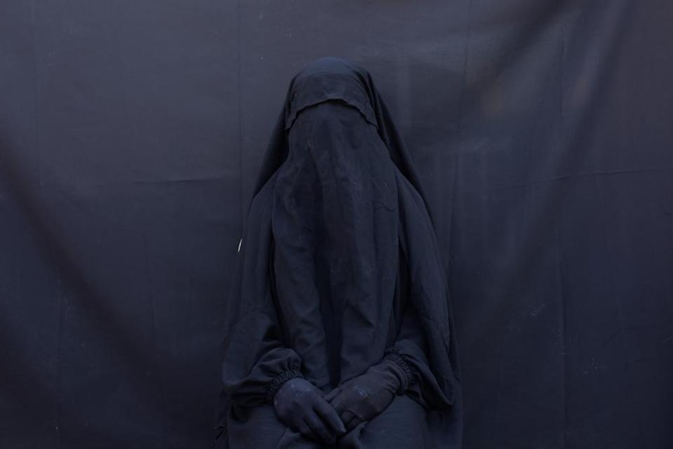 Yazidi Layla Taloo poses for a portrait in the full-face veil and abaya she wore while enslaved by Isis militants, at her home in Sharia, Iraq.