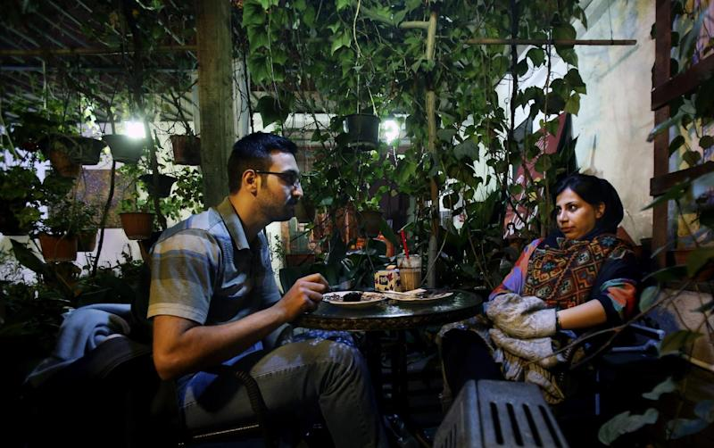 """In this Tuesday, March 4, 2014 photo, an Iranian woman meets with her friend at a cafe in Tehran, Iran. For years Iranian authorities kept the number of cafes limited since they were seen as a symbol of Western influence and places to spread non-Islamic beliefs. But reports of cafes being shut because they violate """"Islamic dignities"""" have dropped markedly in recent months, suggesting a growing tolerance by the authorities. (AP Photo/Vahid Salemi)"""