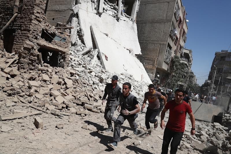 Syrians run for cover during reported government air strikes in the rebel-held town of Douma, east of the capital Damascus (AFP Photo/Abd Doumany)
