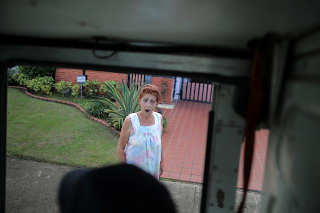 <p>A local resident reacts as a mail man from the U.S. Postal Service arrives at her house at an area affected by Hurricane Maria in San Juan, Puerto Rico, Oct. 6, 2017. (Photo: Carlos Barria/Reuters) </p>