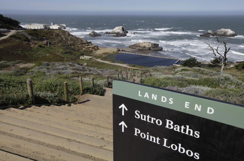 In this photo taken Thursday, May 24, 2012, a sign lead down the path to the ruins of the Sutro Baths at Lands End in San Francisco. At left is the Cliff House. (AP Photo/Eric Risberg)