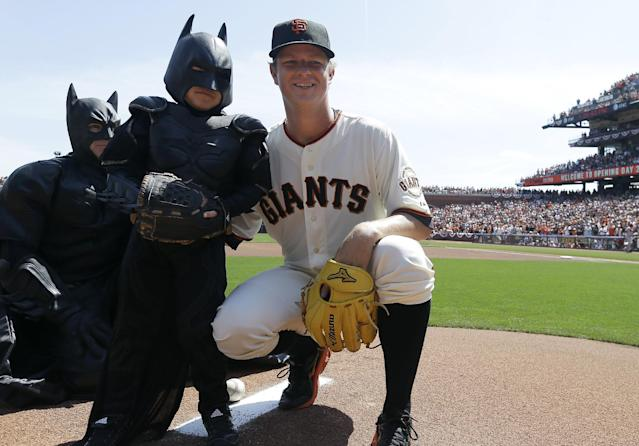 Miles Scott, left, dressed as Batkid, poses for photographs with San Francisco Giants pitcher Matt Cain after throwing the ceremonial first pitch before a home opener baseball game between the Giants and the Arizona Diamondbacks in San Francisco, Tuesday, April 8, 2014. On Nov. 15, 2013, Scott, a Northern California boy with leukemia, fought villains and rescued a damsel in distress as a caped crusader through The Greater Bay Area Make-A-Wish Foundation. (AP Photo/Eric Risberg, Pool)