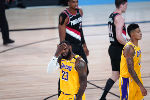 Los Angeles Lakers forward LeBron James (23) reacts to a foul by Portland Trail Blazers guard Damian Lillard (0) during the first half of an NBA basketball game Tuesday, Aug. 18, 2020, in Lake Buena Vista, Fla. (AP Photo/Ashley Landis, Pool)
