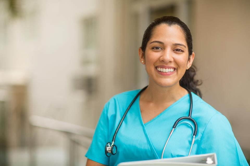 Smiling female healthcare professional looks at the camera while in hospital hallway. She is standing with her arms crossed.