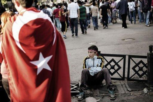 A young Turkish protester rests as others demonstrate, on June 6, 2013, at Kizilay Square, in Ankara