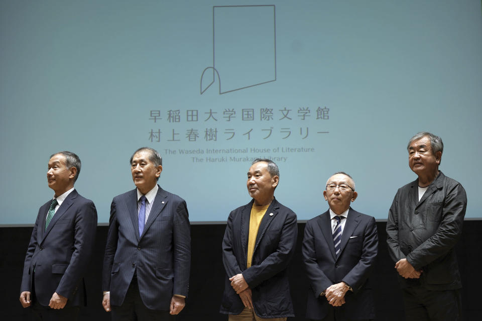 Japanese novelist Haruki Murakami, center, Chairman, President and CEO, UNIQLO CO., LTD. Tadashi Yanai, second right, and Kengo Kuma, right, the architect behind the Olympic stadium, and other university officials pose for media during a press conference on the university's new international house of literature as known as The Haruki Murakami Library at the Waseda University Wednesday, Sept. 22, 2021, in Tokyo. (AP Photo/Eugene Hoshiko)