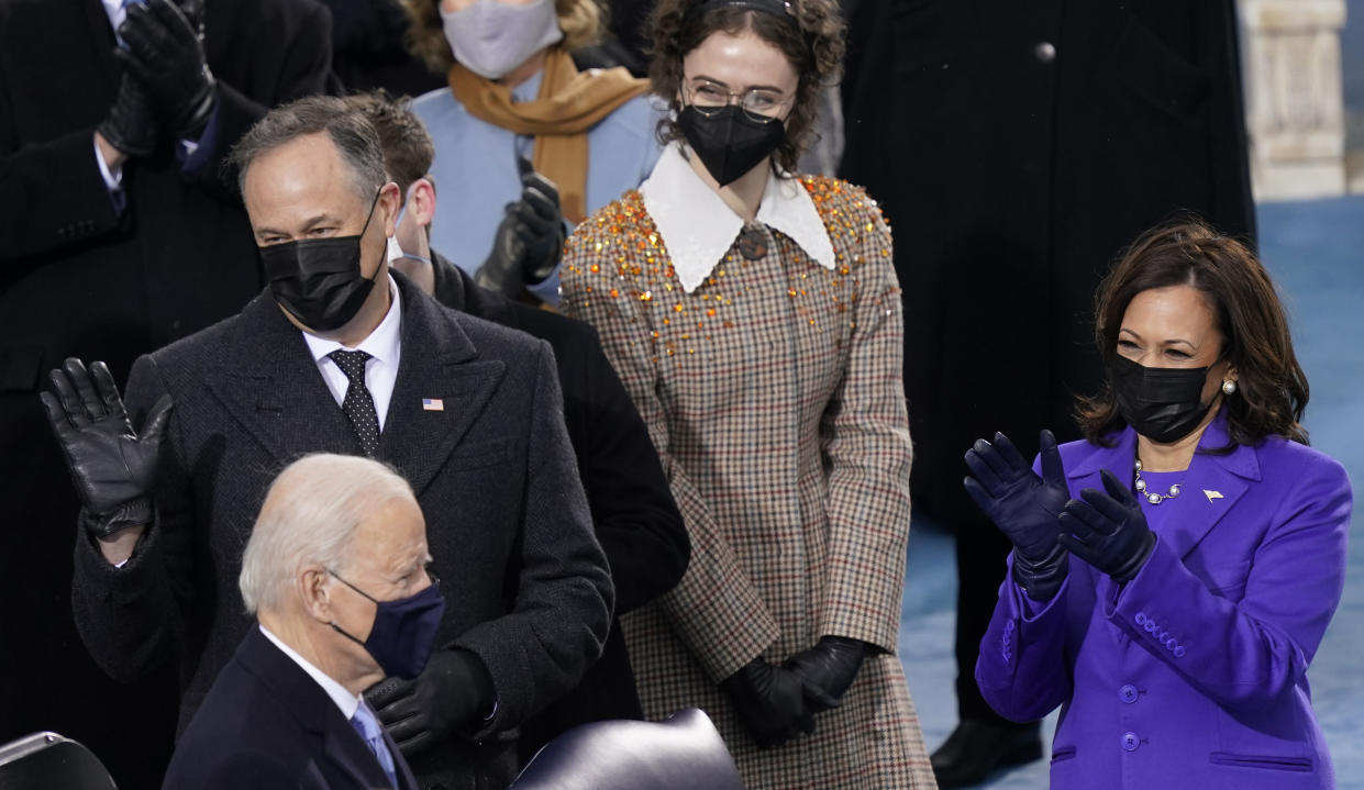 FILE - Ella Emhoff, background center, stands with her stepmother, Vice President-elect Kamala Harris, right, and her father Doug Emhoff, left, as President-elect Joe Biden arrives for the 59th Presidential Inauguration at the U.S. Capitol in Washington, on, Jan. 20, 2021. The designers at Proenza Schouler decided to dress Ella Emhoff in a couple of coats (plus a pantsuit) for her modeling debut in their new collection, unveiled Thursday for New York Fashion Week. (AP Photo/Carolyn Kaster, File)