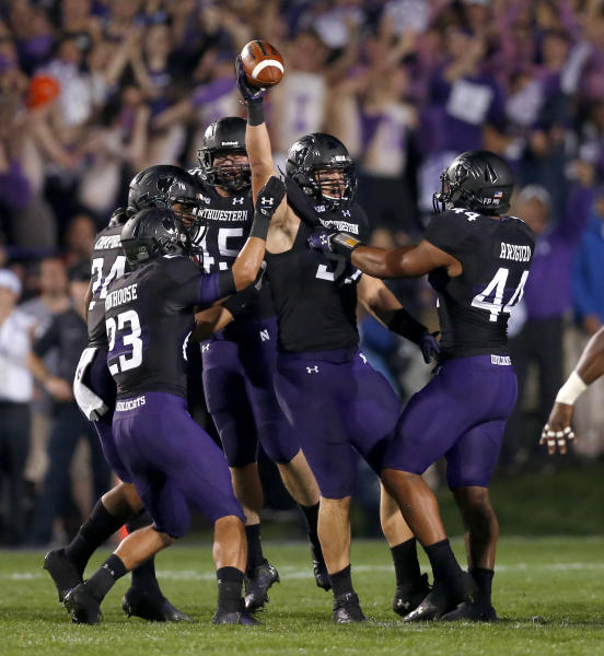 Northwestern defensive lineman Tyler Scott holds the ball up after causing a fumble by Ohio State quarterback Braxton Miller namduring the first half of an NCAA football game Saturday, Oct. 5, 2013, in Evanston, Ill. (AP Photo/Charles Rex Arbogast)
