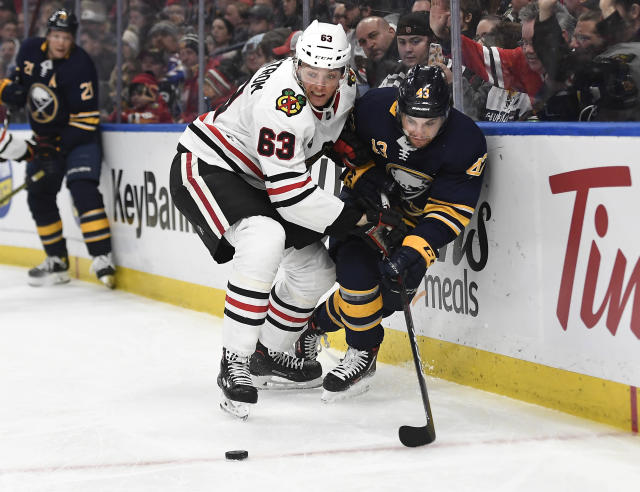 Buffalo Sabres left wing Conor Sheary, right, and Chicago Blackhawks defenseman Carl Dahlstrom vie for the puck along the boards during the second period of an NHL hockey game in Buffalo, N.Y., Friday, Feb. 1, 2019. (AP Photo/Adrian Kraus)