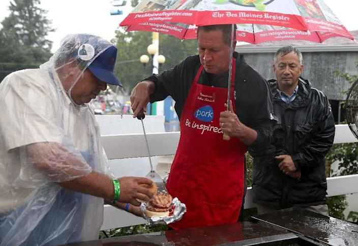 Republican presidential candidate and Ohio Governor John Kasich (R) works the grill at the Iowa Pork Producers Pork Tent during the Iowa State Fair on August 18, 2015 in Des Moines, Iowa (AFP Photo/Justin Sullivan)