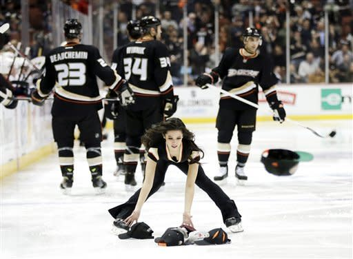 A member of the Anaheim Ducks Power Players picks up thrown caps on the ice after right wing Kyle Palmieri's hat trick against the Nashville Predators during the second period of an NHL hockey game in Anaheim, Calif., Wednesday, Feb. 27, 2013. (AP Photo/Chris Carlson)
