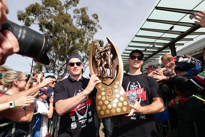 Luke Keary and Sam Verrills hold up the NRL premiership trophy in front of a crowd.