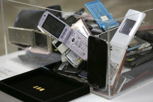 FILE - In this April 1, 2017, file photo, gold tablets of 3 grams, left, which is able to be recycled from 100 mobile phones, are shown as example in Tokyo. Earlier, Tokyo Olympic organizers announced their gold, silver, and bronze medals would be made of discarded electronic devises. Now, they are going a step further. The podiums that athletes will mount to receive their medals next year in Tokyo will be made primarily of recycled household plastics (AP Photo/Eugene Hoshiko, File)
