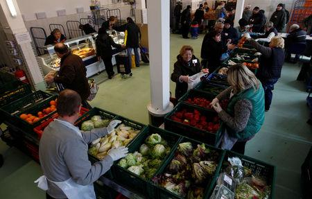 "FILE PHOTO: People receive food that is either too old or not looking nice enough for sale at the non-profit Dortmund food bank ""Dortmunder Tafel""  in the western German city of Dortmund March 20, 2013.  REUTERS/Ina Fassbender/File Photo"