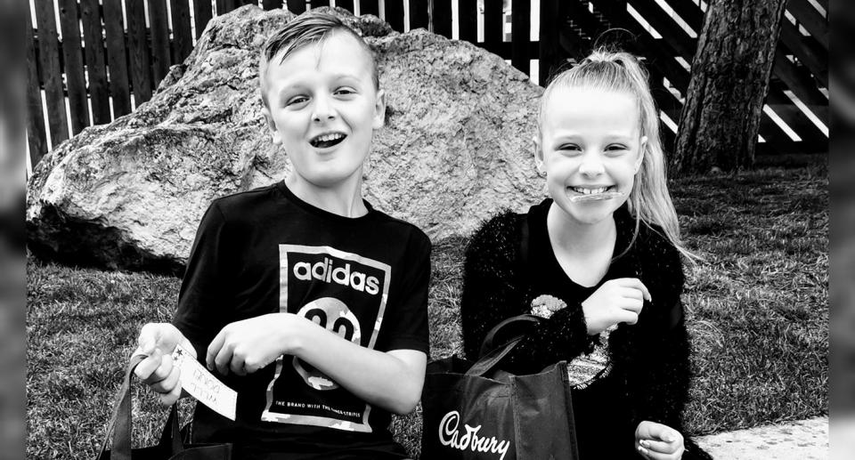 A black and white photo of John and Lacey Bennett sitting down holding bags with Cadbury written on them.