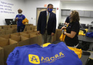Dr. Richard Jensen, CEO at Agora Cyber Charter School, center, talks with Chris Moser, lead family coach in the northeast US, as she and other staff fill boxes with Agora supplies for family coaches to distribute to students, Wednesday, Aug. 4, 2021, in King of Prussia, Pa. (AP Photo/Jacqueline Larma)